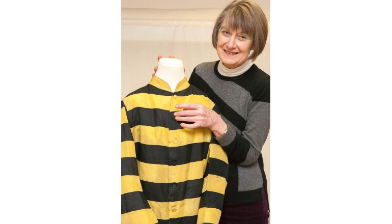 A volunteer at Petersfield Museum with a yellow and black striped jockey's racing silk on a mannequin.